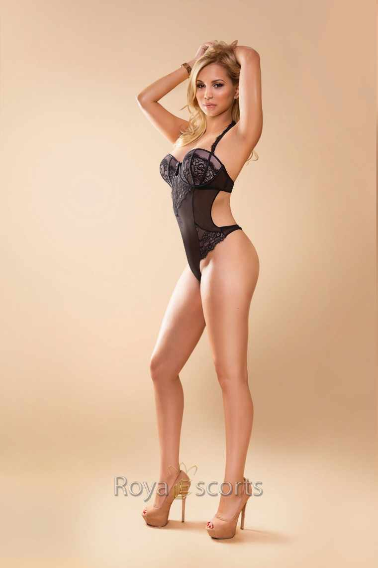 sensual blonde girl wearing a reveling one piece top with her arms raised