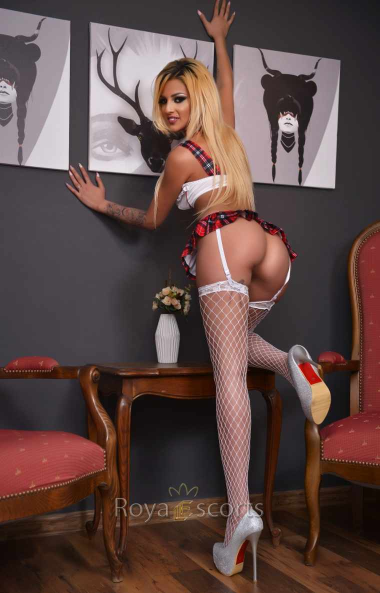 Escort in white stockings kneeling provocatively on a chair
