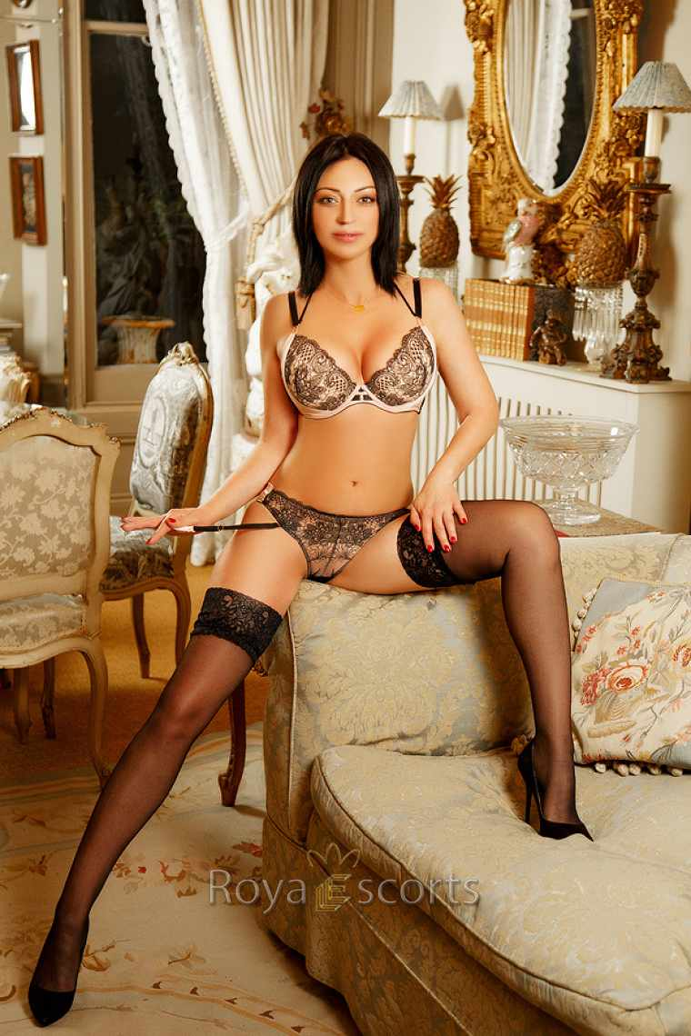 erotic escort reclining on settee with legs open seductively
