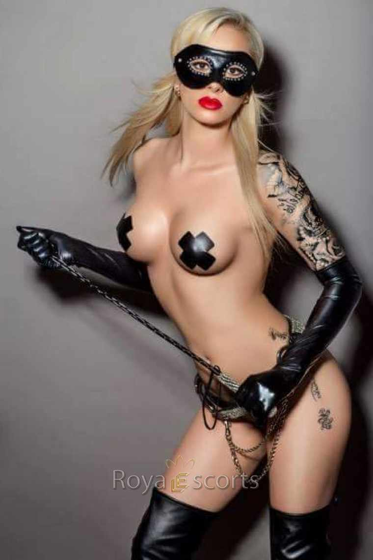 Blonde slim and busty blone escort in BDSM outfit with mask and whip and red lipstick and tattoo