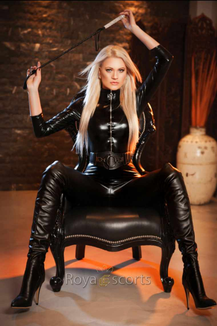 beautiful blonde in vinyl cat suit holding a whip