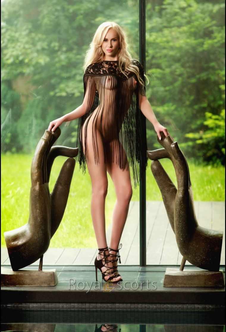 Charming tall blondy semi naked in high heel standing between budha hands overlooking green garden