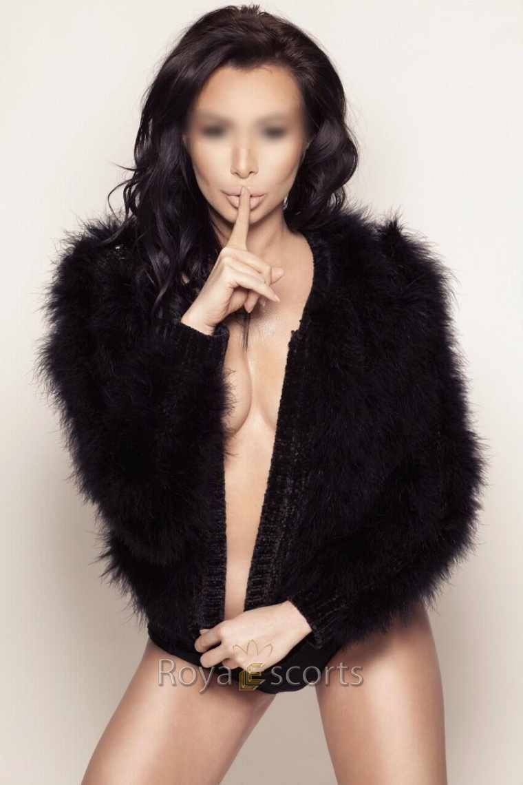 Brunette female escort wearing sensual fur coat