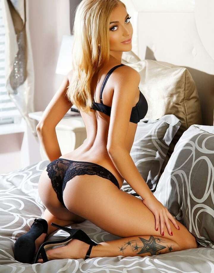 sexy blonde female Bayswater escort kneeling on a bed