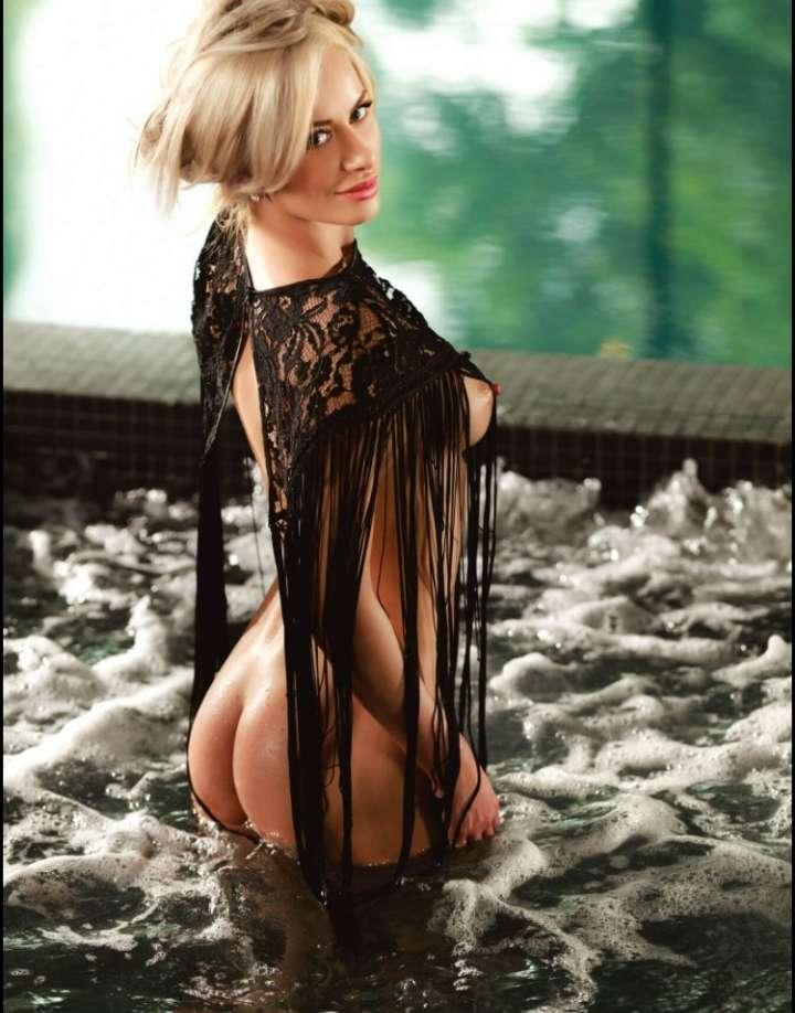 blonde wearing black top in bubbling jacuzzi