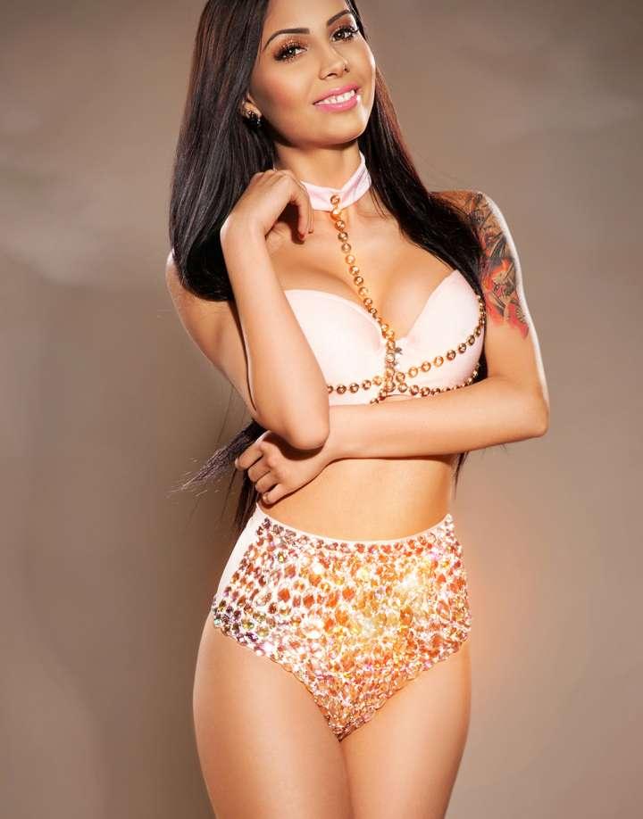 Brunette Marylebone escort in fancy sparkling underwear with tatoo on shoulder standing smiling